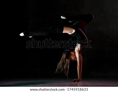 Teenage flexible girl gymnast in black leotard, knee socks and ballet shoes, performing exercises standing on her hands, upside down, posing isolated on bark. Sport, healthy lifestyle. Close-up. #1745918633