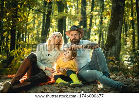 A young family with small child having picnic in autumn nature at sunset. Happy family of three lying in the grass in autumn. Young smiling family doing a picnic on an autumns day