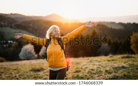 Front view of senior woman hiker standing outdoors in nature at sunset. Royalty-Free Stock Photo #1746068339