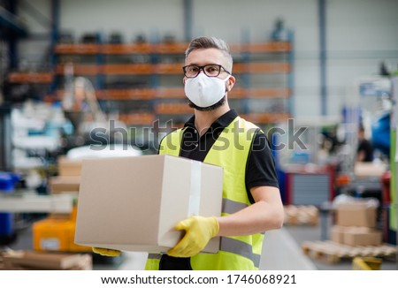 Man worker with protective mask working in industrial factory or warehouse. Royalty-Free Stock Photo #1746068921