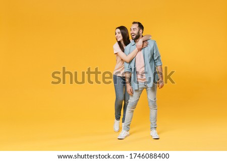 Cheerful young couple two friends guy girl in pastel blue casual clothes posing isolated on yellow background studio portrait. People lifestyle concept. Mock up copy space. Hugging, looking aside