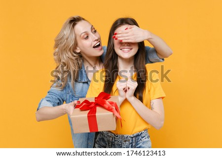 Funny young women girls friends in casual t-shirts denim clothes isolated on yellow background. Women's Day birthday, holiday concept. Hold present box with gift ribbon bow, covering eyes with hand