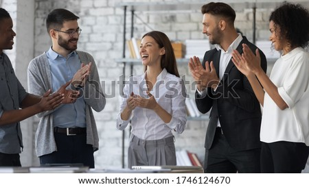 Friendly diverse employees congratulating businesswoman with business achievement, great work results or job promotion, business people applauding and cheering, standing in modern office #1746124670