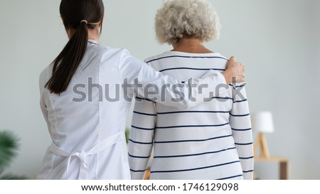 Rear back view young caregiver in white coat supporting hugging elderly patient help her to walk, physiotherapist and physiotherapy activity, provide assistance to old woman, homecare nursing concept Royalty-Free Stock Photo #1746129098