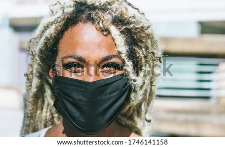 Portrait of african girl with blond dreadlocks wearing face protective mask for Coronavirus prevention - Covid 19 lifestyle and trendy people concept - Focus on face #1746141158