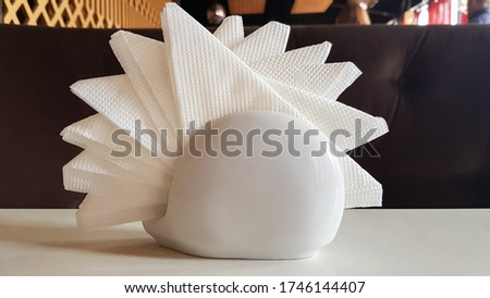 A table in a cafe and restaurant. White napkins in a ceramic napkin holder. Hotel dining table with napkins. A paper napkin is placed in a glass on a table in the banquet room. #1746144407