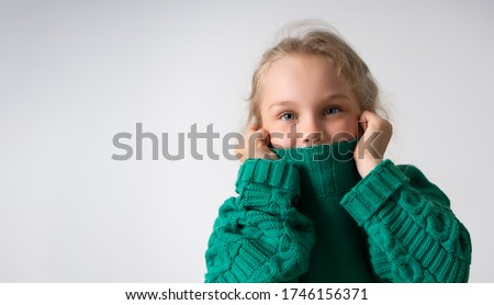 Adorable little girl hiding lower part of her face under thick collar of warm knitted sweater. Children, gesturing and emotions, happiness, winter. Close up studio shot isolated on white, copy space Royalty-Free Stock Photo #1746156371