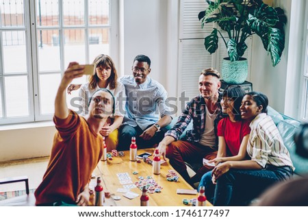 Young male and female bloggers clicking media pictures for sharing to web social networks, millennial poker players shooting influence video during cellular phoning in cozy home interior for gathering