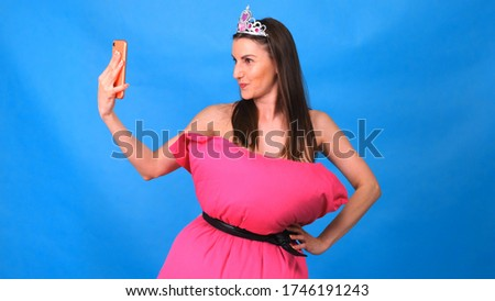 The most beautiful girl in a pink dress from pillows makes a selfie on a blue background. Crazy quarantine. Fashion 2020. Put on a pillow. Challenge 2020 due to house isolation.