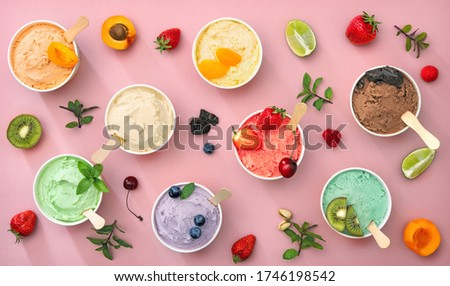 Various colorful ice cream sorts with fruits in paper cups on pink background