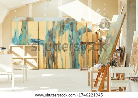 Background image of empty art studio in attic lit by sunlight, focus on easel and abstract paintings, copy space