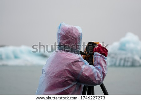 Photographer wearing a raincoat takes a picture in Iceland with a small iceberg floating in the lake.