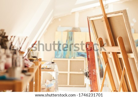 Warm-toned background image of empty art studio interior lit by sunlight, focus on easel in foreground, copy space