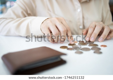 Hands of desperate asian woman is counting her last remaining coins from her wallet on white table,poverty and absence of money,unemployed,financial problems,economic crisis from Covid-19 pandemic #1746251132