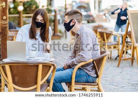 Student youth hipster man and young woman in facial masks drinking coffee at an outdoor bar cafe or restaurant. New normal concept reopening after quarantine concept. #1746255911