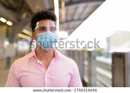 Young Indian businessman with mask and face shield waiting at the sky train station Royalty-Free Stock Photo #1746316646