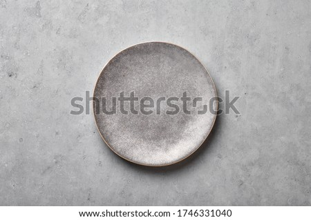 Gray ceramic plate on grey concrete rough background. Empty spotted uneven saucer. Matte dish on stone textured backdrop. Hand made ceramic table setting. Top view #1746331040