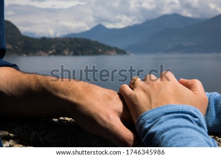 Couple. You can see the hands touching each other. Sensually.Water and mountains in the background. #1746345986