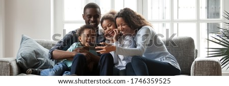 Full African family with little kids sit on couch in living room having fun using smart phone new cool application, taking selfie, watch funny videos. Horizontal photo banner for website header design