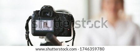 Close up on professional dslr camera filming new videovlog woman vlogger. Business coach gives lecture, live training on-line, commercial ad concept. Horizontal photo banner for website header design