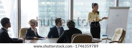 Asian businesswoman coach makes presentation for multi-ethnic international company staff using flip chart. Corporate training, negotiations concept. Horizontal photo banner for website header design