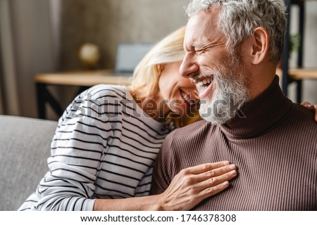 Happy laughing middle aged couple bonding while relaxing sitting on sofa Royalty-Free Stock Photo #1746378308
