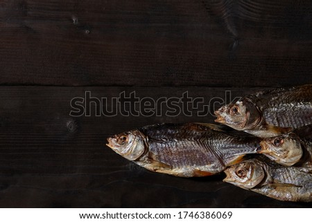 Jerky or dried salted roach, delicious clipfish on wooden background. Popular beer snack. Traditional way of preserving fish. Close up