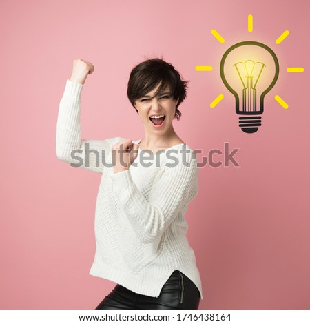 Beautiful young woman with happy expressing winning gesture. Successful girl celebrating victory with light idea bulb above head. Pretty brunette model  and cartoon lamp. Girl finds brilliant solution