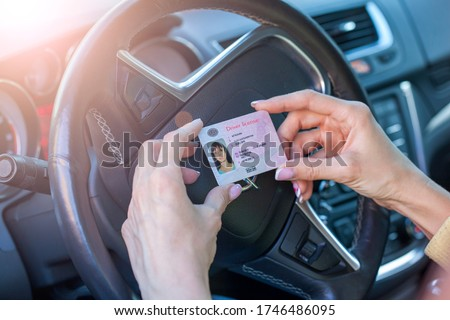 Getting a driver's license, female hands show US driving license, amid the steering wheel of a car #1746486095