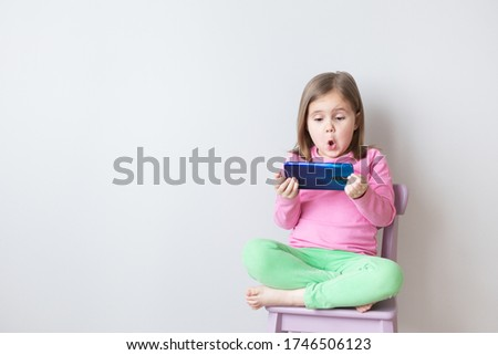 Beautiful caucasian girl watching a cartoon on a smartphone. Very surprised. Gray background.