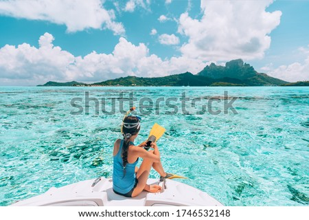 Snorkel diving excursion boat tour from yacht luxury travel influencer going swimming in coral reefs of Tahiti, French Polynesia Bora Bora island. #1746532148