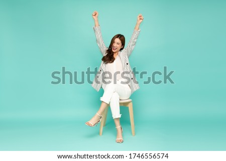 Attractive beautiful Asian woman sitting on white modern chair and hands up raised arms from happiness, Excited businesswoman winner success concept #1746556574