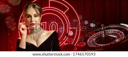 Girl in jewelry and black dress. Showing two red chips, posing on colorful background with neon lights, roulette and chips. Poker, casino. Close-up #1746570593
