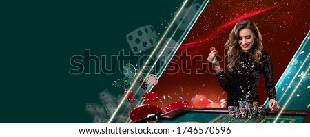 Smiling model in shiny black dress. Showing two red chips, posing at playing table on colorful background with flying money and dices. Poker, casino Royalty-Free Stock Photo #1746570596