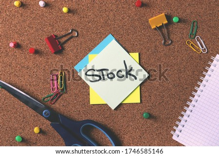"rustic cork board with a stick up note ""stock"" representing the idea of reminding about stock"