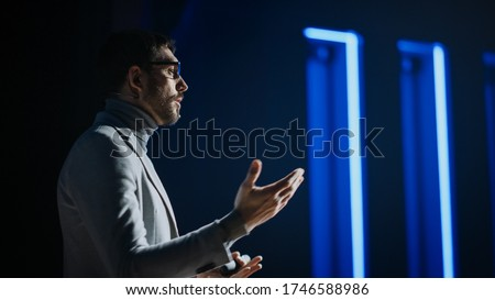 Portrait of Motivational Speaker Wearing Glasses, Talking about Happiness, Self, Success and How Better More Productive Self. Tech Startup Presenter Pitching. Cinematographic Light #1746588986