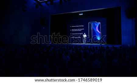Live Event with Brand New Products Reveal: Keynote Speaker Presents Smartphone Device to Audience. Movie Theater Screen Shows Mock-up Touch Screen Phone with High-Tech Features and Top Highlights #1746589019