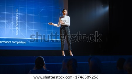 On Stage: Inspirational Female Speaker, Talking about Happiness, Self, Success, Efficiency, Health, and How to Be More Productive. Tech Industry Business Conference Auditorium Hall full off People #1746589256