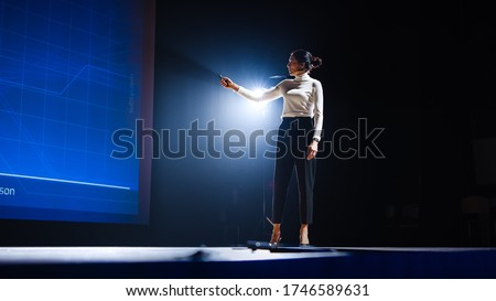 On-Stage Successful Female Speaker Presents Technological Product, Uses Remote Control for Presentation, Showing Infographics, Statistics Animation on Screen. Live Event / Device Release. Royalty-Free Stock Photo #1746589631