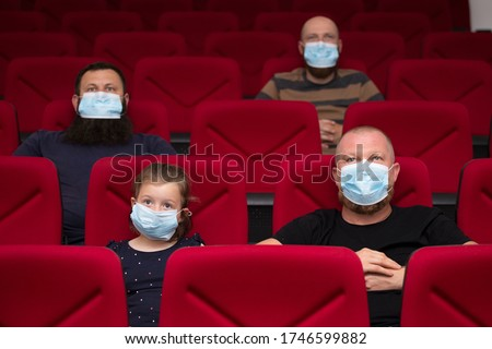 People in cinema with protection mask keeping distance away to avoid physical contact.Coronavirus COVID-19 disease protection.Social distancing practice #1746599882