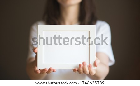 person holds white frame in her hands. woman in white t-shirt on dark background. mockup fot text ad
