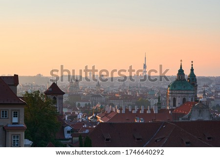 Beautiful morning picture over the Prague old town during early spring sunrise. Picture show rooftops of historic buildings and towers with dome of Saint Nicolas church in Lesser Town under the Castle
