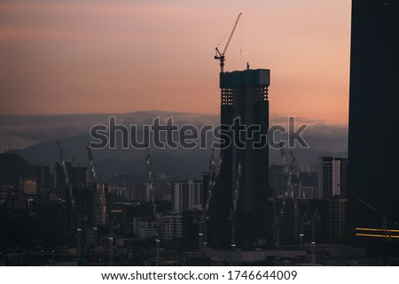 Construction of a skyscrapers block in the center of Kuala Lumpur, Malaysia. Many tower cranes build skyscrapers. Dawn photo with the background of cloudy hills. #1746644009