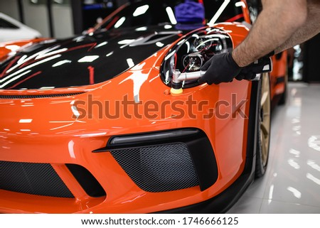 Car detailing - Worker with orbital polisher in auto repair shop. Selective focus. Royalty-Free Stock Photo #1746666125