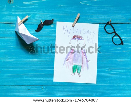 Children's drawing of super hero dad, paper boat, paper mustache and glasses on a string, aquamarine wooden background