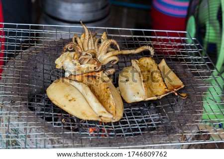 Grilled Cuttlefish on a charcoal stove. Grilled squid is very tasty.Can found at street food,Thailand. BBQ Grill On Hot Charcoal.Grilled fresh squid on a grill with charcoal grill. #1746809762