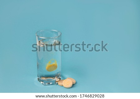 Glass of water and pills on a blue background close-up. A tablet of vitamins is dissolved in water. Copy space.