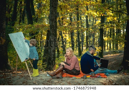 Outdoor family vacation at autumnal golden forest. Family of three spending time together at autumn park. Mum is talking by phone, dad using laptop and little son is painting a picture