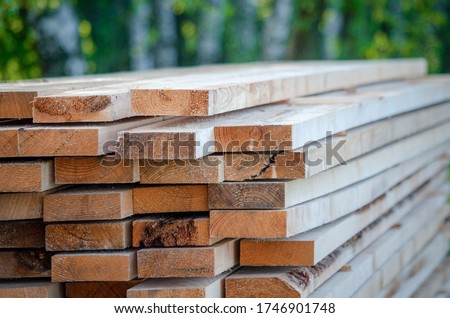 Builder in a protective helmet holds wooden planks. Concept - sale of lumber. Builder is considering wood planks. Concept - wood processing business. wood timber stack of wooden planks. #1746901748