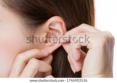 A young woman is massaging her ears. Royalty-Free Stock Photo #1746903536